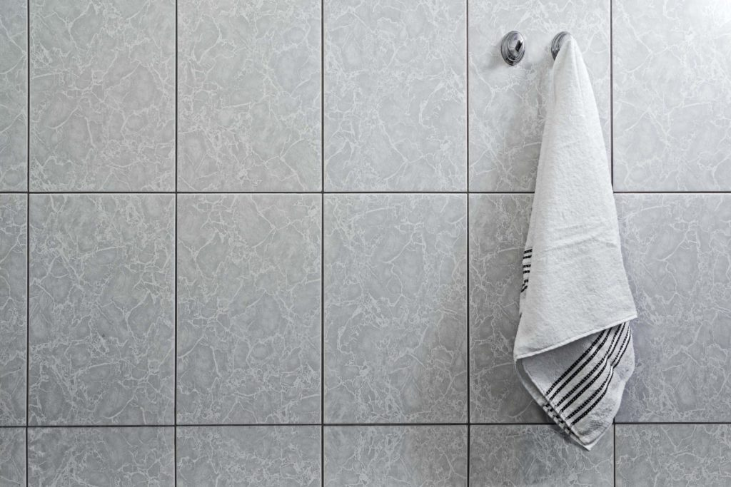Towel hanging on a hook against the background of a tiled wall, the theme of cleanliness and hygiene