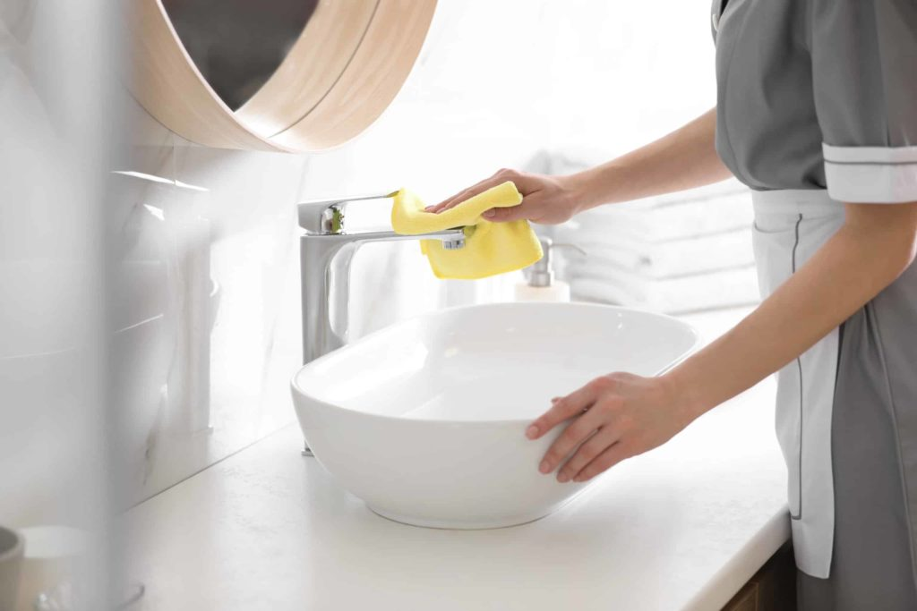 maid cleaning hotel bathroom
