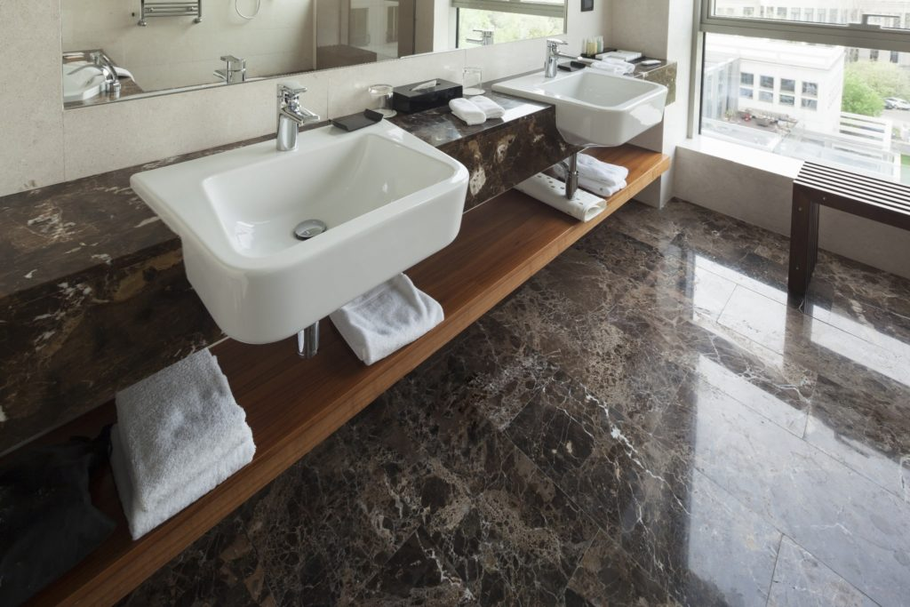 Brown marble floors and counters in a hotel bathroom.