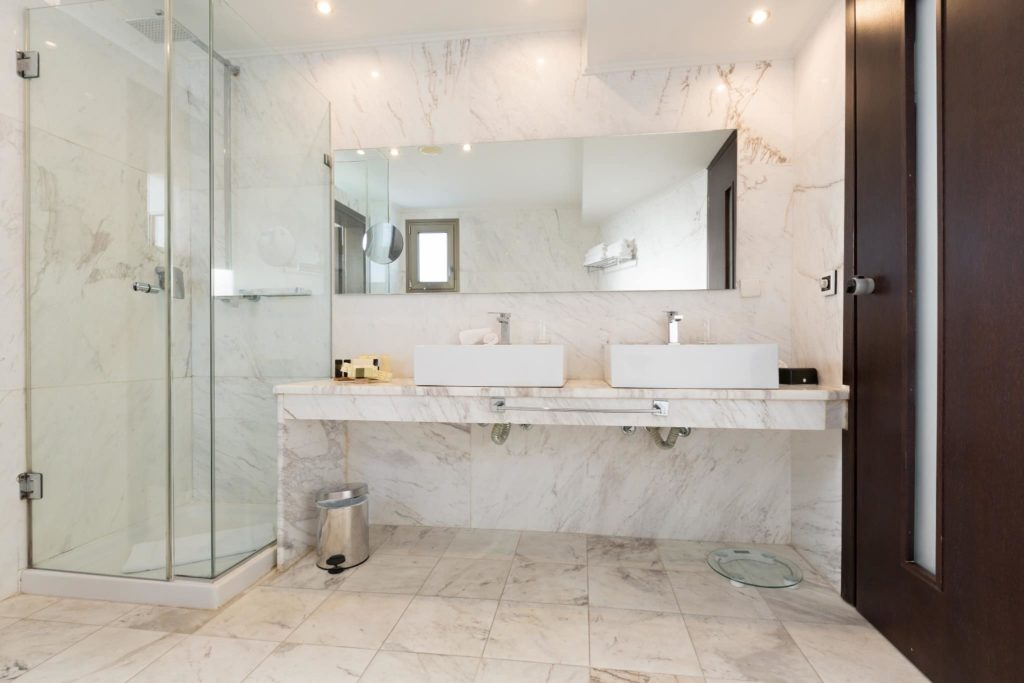 A hotel bathroom with marble walls and floors looks beautiful after marble restoration.