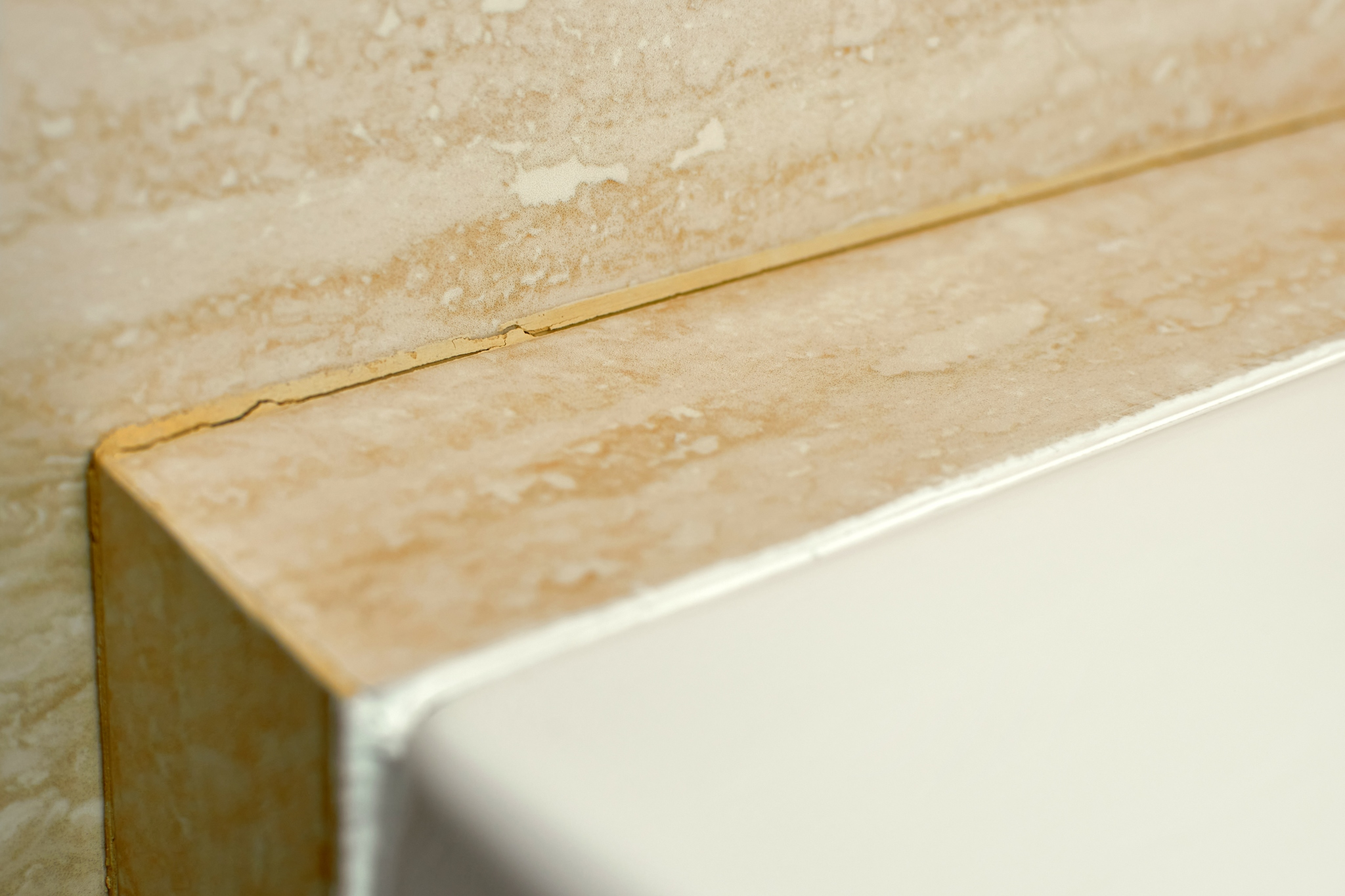 How long should grout last before cracking? Cracked grout along a countertop.